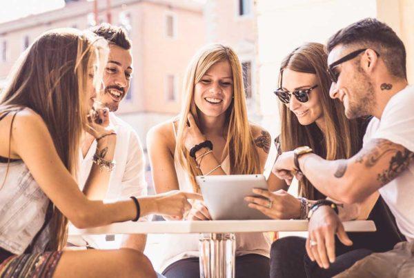comunicazione-integrata-ragazzi-che-discutono-di-un-brand-e-guardano-un-tablet